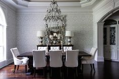 Formal dining room with a Crystal and Iron Adrian Chandelier hung from an octagonal tray ceiling over a dark stained trestle dining table lined with white tufted side chairs with nailhead trim.