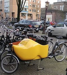 XL yellow Dutch wooden shoe on a bicycle in Amsterdam