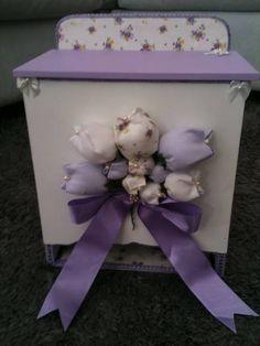 Porta fraldas em mdf, coleção tulipa,  forrado internamente com tecido floral branco e lilás, pintado externamente de branco e lilás com aplicação de buquê de tulipas de tecido, finalizado com um laço de fita de cetim,  formando um lindo conjunto romântico e delicado. Acabamentos com passamanarias e lacinhos.  Junto com este porta fraldas pode-se adquirir o kit de higiene, a caixinha, o trocador, almofadinha e o trio de quadrinhos, formando um conjunto muito delicado para o quartinho do…