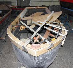 Many clamps are used to hold plywood laminations in place while epoxy glue hardens during the updates to guest boats at WaterFire Providence.