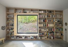 chalet forestier designed by atelier barda & lise gagné - bookcase does a wonderful job of framing the window
