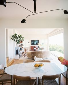 Living Room Modern Photo - An oval marble table and wooden chairs with woven seats in a dining nook