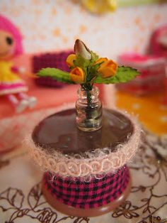 The table is a rubber furniture leg cover altered with ribbon trims and the vase is miniature bottle with paper flowers and leaves. Lalaloopsy, Miniature Bottles, Furniture Legs, Miniature Furniture, Minion, Dollhouse Miniatures, Paper Flowers, Lunch Box, Diy