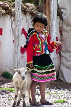 This sweet child and her lamb were walking in the market on a cool fall afternoon near Pisac, Peru. Photo by WorldTravelPhotos.