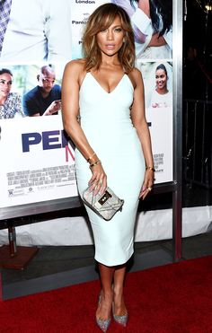 J lo is wearing a white Cushnie et Ochs fitted midi dress with glitter pointy toe pumps and a black and white print clutch. This dress fits her perfectly. The white pops against her skin tone.