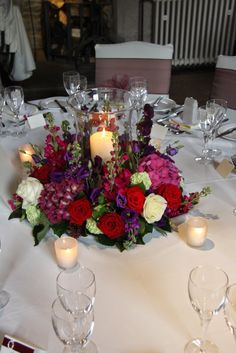 Candlelit Hurricane Lamp surrounded by a luscious collection of rich jewel toned blooms