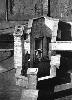Photo by André Kertész, Woman in Window Looking Down Air Shaft, 23rd Street, New York, 1970