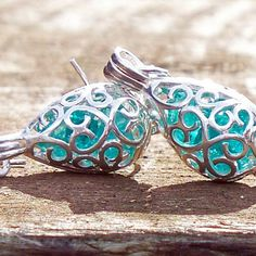 STUNNING!  Who knew recycled could be so beautiful!  From the broken remains of vintage bottles and glass come these lovely filigree teardrop earrings.  Glass has been reclaimed from these habitats, pounded down and sparlkes inside the pretty filigree setting.  Filigree pattern is all around allowing light to pass through and illuminate the glass (and the person wearing them).	 Available in a beautiful rainbow of colors including:	cobalt from broken Noxzema ...
