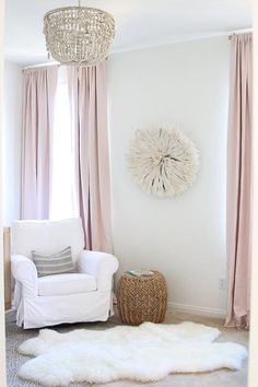 White and pink nursery features walls painted soft white, Benjamin Moore White Dove, lined with a white glider with rolled arms, PB Kids Comfort Grand Swivel Rocker, and a Crate & Barrel Izzy Stool, is placed atop a sheepskin rug layered atop a gray rug, Urban Outfitters 4040 Locust Gale Geo Printed Rug, placed in front of a window dressed in soft pink curtains, RH Baby & Child Linen Cotton Drapery Panels Petal, on a brass curtain rod, Umbra Cappa Decorative Window Curtain Hardware…