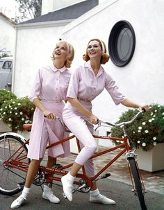 Models in pink summer fashions on a Schwinn tandem. 1964.