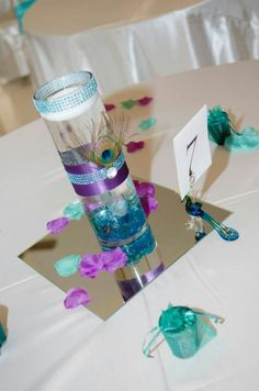 Table Centerpieces made by me. Peacock theme glass vase embellished with acrylic gems ,satin ribbin and a peacock feather Peacock Wedding Centerpieces, Wedding Decorations, Table Centerpieces, Sweet Delivery, Baby Shower Table Decorations, Acrylic Gems, Peacock Theme, 50th Party, Flower Arrangements