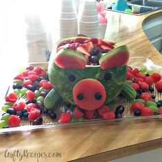 How cute is this watermelon pig!? Just cut the top off of the watermelon and scoop all the insides out. Cut cucumbers to look like legs and stick them in with a toothpick. Cut a circle out of the extra rinds and flip it backwards to look like a pig's nose. Add grapes or blueberries …