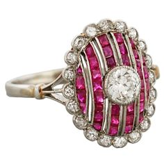 A stunning diamond and ruby ring from the Edwardian (ca1910) era! This gorgeous ring is made of platinum topped 14kt yellow gold and has a stunning old Mine Cut diamond bezel set in its center. The center diamond is set atop a bed of 6 graduating rows of natural, calibrated cut rubies. Framing the entire, oval-shaped ring are 20 single cut diamonds which complete the gorgeous piece beautifully. C. 1910