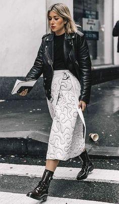 Street style look com saia midi, jaqueta de couro e coturnos