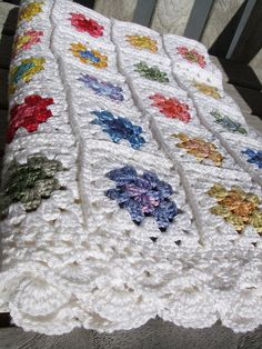 Baby blanket - white granny squares. with colored 'flowers' in center of squares. Gotta do this!!