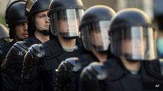 Following Days Of Protests, Cleveland Strikes Deal With Justice Dept Over Police Brutality Riot police stand in formation as a protest forms against the acquittal of Michael Brelo, a patrolman charged in the shooting deaths of two unarmed suspects in Cleveland.