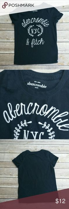 """Abercrombie & Fitch Navy Kids Logo Tee Size 3/4 Abercrombie &Fitch short sleeve navy blue knit tee with raised cursive signature style logo on front . Excellent condiiton . Tagged size 3/4 .  Styled with our tiny joes jeans and puffer vest. Also for sale in our closet.  Measurements : Length 15 1/2"""" 11"""" across front laying flat unstretched #ravenkittyminis #abercrombie #a&f #kids #navyblue #logo #trendy #mall #size3 #size4 #casual #prep #prepster #preppykid #fashionista #layer #backtoschool…"""