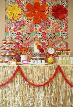 Hawaiian Luau theme - The focal point, a backdrop made of a colorful bed sheet from Pottery Barn Teen!  Table skirt using raffia hula skirts and added garland using leis from Party City.  Gorgeous clay hibiscus from DK Designs dressed up a homemade cake.