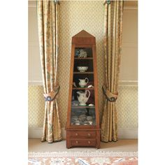 A stained pine display cabinet in the form of an obelisk with a glazed door and two drawers to the plinth 200cm. high; 61cm. wide, 45cm. deep; 6ft. 6¾in., 2ft., 1ft. 5¾in.