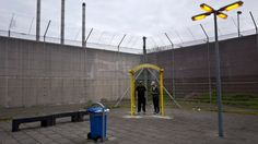 Algerian migrant Mohammed Ben Salem, 36, and Libyan Amine Oshi, 22, smoke a cigarette at a yard of the former prison of De Koepel in Haarlem
