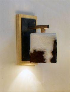 Lampada da parete su basetta, in legno, supporto in ferro anticato e paralume in mucchetta.