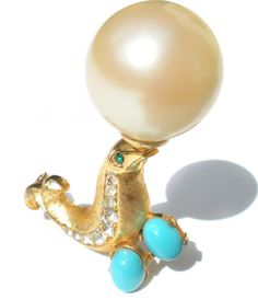 ❘❘❙❙❚❚ ON SALE ❚❚❙❙❘❘     This fun figural brooch features a seal balancing a beach ball faux pearl. Brushed gold tone metal is inlaid with a channel of rhinestones down the belly and it appears to be holding two small turquoise cabochons. It is signed A1501 which Ive been unable to link to a maker.  Measurements: 1 7/8 Tall x 1 3/4 Wide (at widest points)  Please be sure to check out my shop for a *~HUGE~* variety of vintage non-pierce earrings and jewelry that has FREE additional ...