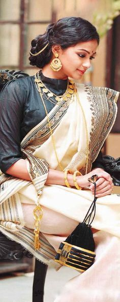 Traditional bengali style saree draping and jewellery. Note the trinket attached to the end of the saree pall to hold keys of the house. Usually the mistress of the house would carry the main keys in this way. The heavy trinket would also help keep the saree in place when thrown over the shoulder - Sonali.