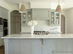 beautiful gray kitchen, white marble tops, white herringbone backsplash, goodman hanging lamps