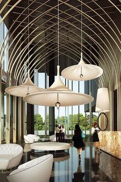 Low hanging lights from a high ceiling are all the rage and are becoming more and more popular. Especially in lobbies. I believe it's because when we look to the ceiling and see the lights we can't see the ceiling but we can sense the echoes so it feels like the top could be going on forever. Also the high windows allow for natural light from the world outside and a fantastic view is excellent to top it all off.