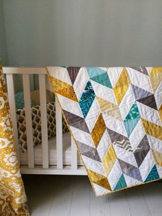 Herringbone baby quilt by https://quiltingstories.blogspot.com/2016/12/herringbone-half-square-triangle-baby-quilt-finished-hand-quilted-yellow-blue-grey.html