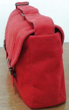 Bolsa estruturada de sarja peletizada na cor vermelha. 2 bolsos internos. Fechamento com botão imã (2 unid.). Ferragens no tom ouro envelhecido. Alça ajustável (102cm). Produzida com material de qualidade: Sarja peletizada, zíper YKK, algodão cru de gramatura elevada e linha Nylon 60.