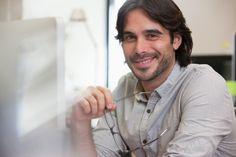 Portrait of smiling businessman holding eyeglasses