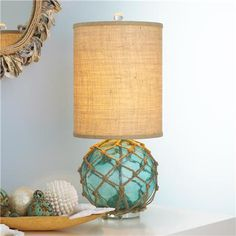 Vintage glass buoy with rope netting sits on an acrylic base and topped with a modern shaped cylinder burlap shade. Nautical, glass buoy, burlap, coastal.