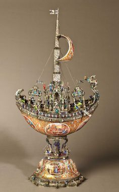 - A Highly Important Viennese Nef by Hermann Böhm Constructed in silver, bears maker's marks- exquisitely enamelled-boat form nef, with detachable enamelled cover, with enamelled ellipses, polychrome decorated stem cast with four stylised dolphins interspersed with tritons, & incorporating a pavilion of musicians/spectators/six oarsmen; a central mast, under sail, and dressed with spirally decorated enamels, topped with a flag Vienna, Circa 1880