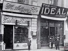 Los vecinos locales de M. Artigas y The IdealShoe, competían en la calle Ahumada por captar la atención de los clientes con llamativas vitrinas, llenas de zapatos importados de Inglaterra, Estados Unidos y Suiza. Fotografía en Álbum Vistas de Santiago, 1915.