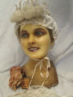 Antique wax mannequin bust with stunning blue glass eyes, used for bridal display.