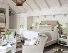 source: Atlanta Homes & Lifestyles  Bungalow 5 Polo Side Tables, glass demijohn lamps and upholstered bed with nailhead trim! Striped taupe and white area rug, conversation area with pinstriped Lee Industries chairs and white chinoiserie coffee table. Vaulted, white wood ceilings with Solaria Lighting Luigi chandelier