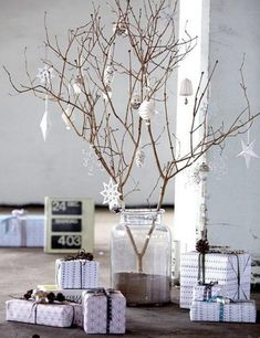 Be as creative as you can be this Christmas with a slim but elegant Christmas tree. Gather twigs across your yard and set them up in a glass jar filled with sand. Hang in white Christmas decor and create more drama with the white wrapped gifts beside it.