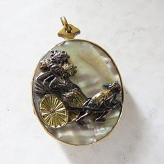 Antique Mother of Pearl Asian Locket Rickshaw Damascene Locket- Gold Filled 1 1/4 x 1  beautiful mother of pearl locket- it is double sided with a metal rickshaw on each side- it is gold filled- or a very low karat gold (9 karat was common in the late 1800s) no way for me to test to be certain  it is 1 1/4 high and 1 wide- the locket and hinges work perfectly- please see all photos