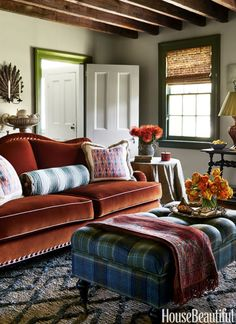 VELVET COUCH – The custom sofa in an 1850s home, designed by Suysel dePedro Cunningham and Anne Maxwell Foster, is covered in a Schumacher velvet and the Ballard Designs ottoman in a Rogers & Goffigon tartan. The trim is painted in Benjamin Moore's Great Barrington Green. Click through for more living room ideas.