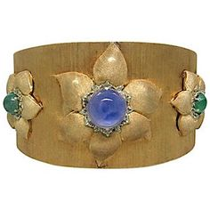 Rare Buccellati 14k yellow gold cuff floral bracelet, c. 1960s, with three flower designs, 14.15ct sapphire cabochon and two emerald cabochons (3.34ctw), $28,000