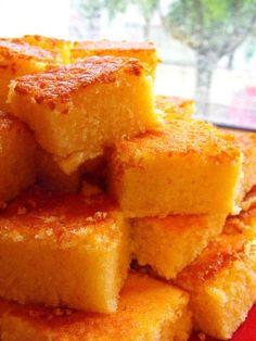 As receitas lá de casa - Quadradinhos de laranja 2 iogurtes naturais 4 ovos 280g de açúcar 100g de margarina vegetal amolecida 350g de farinha de trigo 1 colher de chá de fermento em pó 1 laranja grande - Sumo e raspa  Pré-aquecer o forno a 180.ºC. Untar um tabuleiro pequeno com margarina e polvilhar de farinha. Reservar.  Começar por bater muito bem os ovos com o açúcar. Juntar de seguida os iogurtes, a margarina amolecida, o sumo e a raspa da laranja. Quando estiver uma massa muito lisa e…