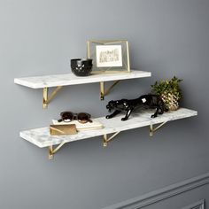 Shop Marble Wall-Mounted Shelves.   Smooth slab of Carrara-style white/grey marble showcases photos, art and objects of interest with natural cool.  Levels out on industrial metal brackets with brass finish.