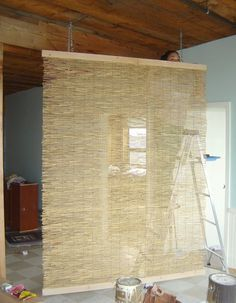 reed fencing and 1x4 boards (The fencing is actually enough to make two 8' long room dividers and at $23 for the entire 16' roll from Home Depot which makes this a very inexpensive DIY project. Room Divider - Paint white or black!