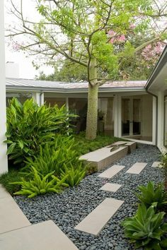 Using black or dark gray as a surface for paths and patios gives a design gravitas. In this example black Mexican beach pebbles juxtaposed w...