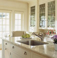 In this soft cream #kitchen the upper cabinets showcase decorative stained glass. Love the mix of old with new and how the antique-inspired stained glass balances the contemporary design elements.