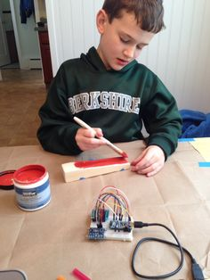 Emmett building the PineDuino using a fresh coat of paint and bread-boarding the car's on-board electronics.