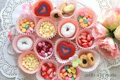 Valentine cupcake papers with candy and cookies in them