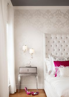 This gorgeous white bedroom feels soft and airy yet glamorous and fashionable. The chic metallic nightstand adds to the glamorous feel, providing contrast against the room's white furnishings.