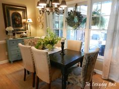 breakfast room, home decor, living room ideas, painted furniture, Black Painted Farmhouse Table a mixture of khaki parson s chairs with two paisley parson s chairs on each end A cute blue cabinet anchors a large print on one side